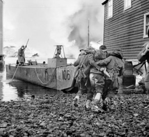 Wounded being helped onto a landing craft