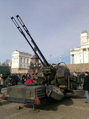 Picture of the twin cannon Rheinmetall GDF at some kind of outdoor exhibition, surrounded by people, with steps in the background leading up to domed and colonnaded white buildings