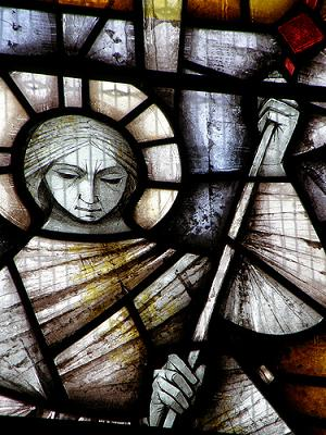 Detail from a stained glass memorial window to Sir Thomas Sopwith, face of an angel wielding a sceptre with cross on top; colours are white, blue, red and yellow.